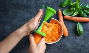 Woman using vegetable spiral slicer to make carrot spaghetti