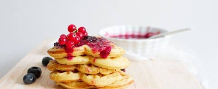 Thin waffles stacked with fruit on top